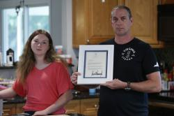 In this May 22, 2020, photo, Jason Nixon, right, holds a letter from President Donald Trump as he poses with his daughter, Morgan, left, as they display memorabilia from last year's shooting that took the life of Kate Nixon