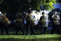 Police watch from Lafayette Park as demonstrators gather to protest the death of George Floyd, Sunday, May 31, 2020, near the White House.