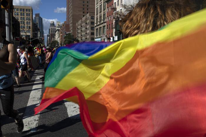 Parade-goers carrying rainbow flags walk down a street during the LBGTQ Pride march in New York, to celebrate five decades of LGBTQ pride, marking the 50th anniversary of the police raid that sparked the modern-day gay rights movement.