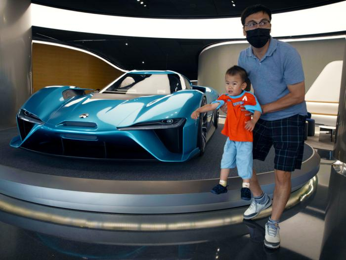 A man lifts a child away from a race car displayed at the NIO flagship store in Beijing on Thursday, Aug. 20, 2020