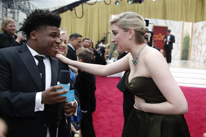 Greta Gerwig, right, talks to Jerry Harris on the red carpet at the Oscars at the Dolby Theatre in Los Angeles.