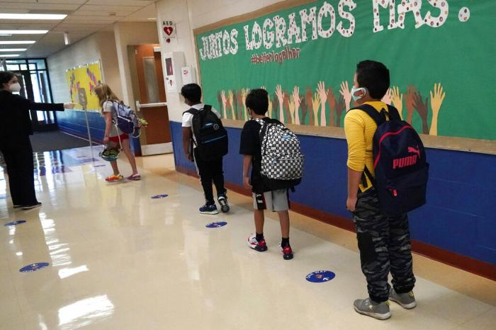 Students keep social distance as they walk to their classroom in Highwood, Ill.