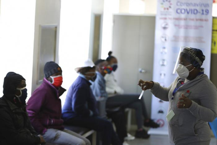A medical worker addresses some of the first vaccine volunteers, at the Chris Hani Baragwanath hospital in Soweto, Johannesburg.