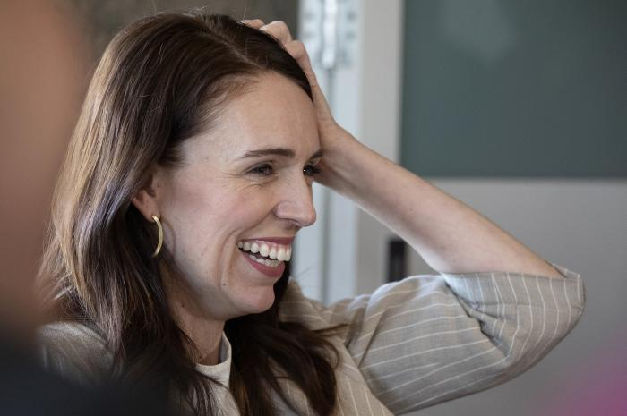 New Zealand Prime Minister Jacinda Ardern reacts as she talks with colleagues at a cafe in Auckland, New Zealand, Sunday, Oct. 18, 2020.