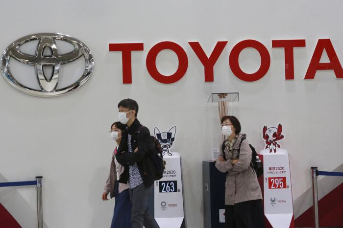 In this Nov. 2, 2020, file photo, visitors walk at a Toyota showroom in Tokyo