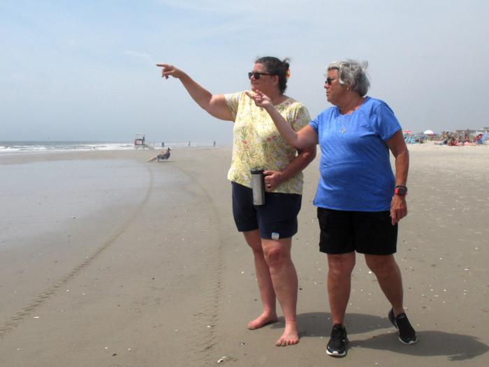 Suzanne Hornick, left, and Susan Cox, right, look out to sea from a beach in Ocean City N.J. on July 8, 2021 where power cables from an offshore wind farm are projected to come ashore