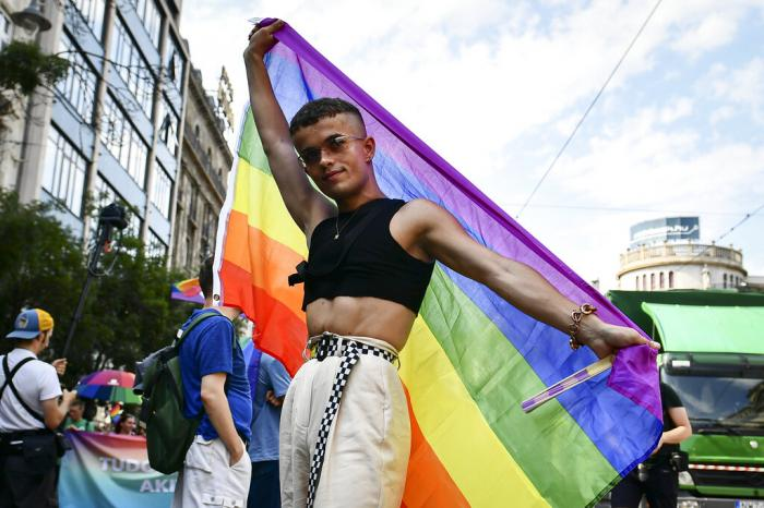 A participant poses with a rainbow flag during a gay pride parade in Budapest, Hungary.